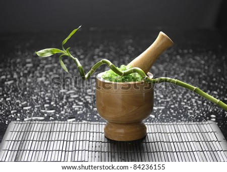 wooden mortar and pestle with lucky bamboo on mat - stock photo