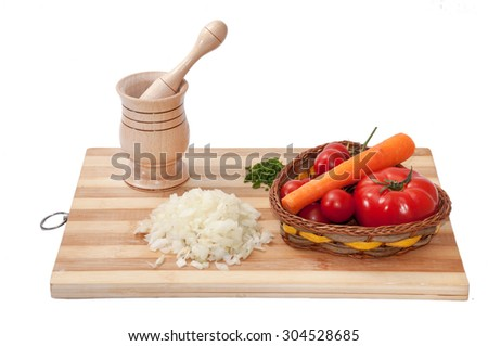 Wooden mortar and tomato, dill, chopped onions and carrot for  food preparation.