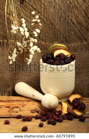 Wooden mortar with dog rose and dried apples - stock photo