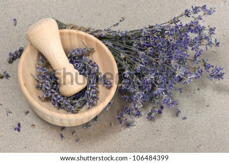 wooden mortar with dry lavender flowers over grungy paper background - stock photo