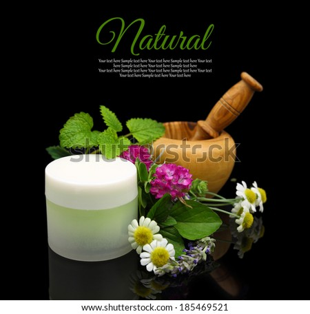 Wooden mortar with herbs and cosmetic cream - stock photo