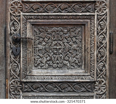 Wooden motifs on a medieval church door - stock photo