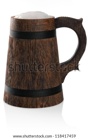 Wooden mug of fresh beer with foam cap isolated on white.