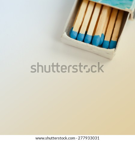 Wooden multicolored, blue matches in vintage matchbox. Retro colors background. copy space. Macro view, toned photo - stock photo