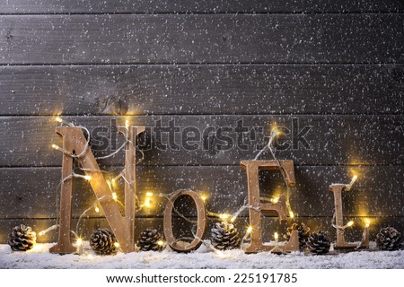 Wooden NOEL with Christmas lights on snow - stock photo