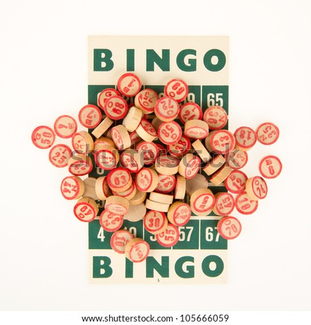 Wooden numbers used for bingo, on top of a bingo card - stock photo