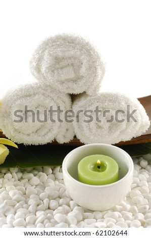 Wooden of roller white towel and bowl green candle on white pebble