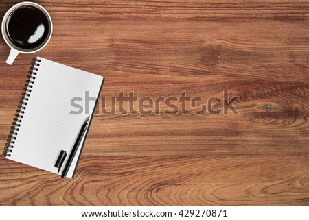Wooden office desk table with notebook, pen and cup of coffee. Top view with copy space. - stock photo