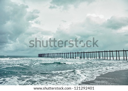 Wooden old jetty over the stormy sea - stock photo