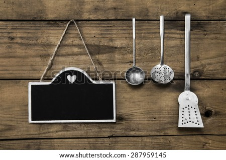Wooden old kitchen background with old kitchenware, blackboard and spoons for cooking fans. - stock photo