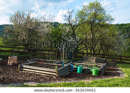 wooden organic vegetable beds with water cans and orchard in rural spring garden - stock photo