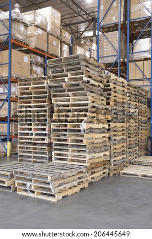 Wooden pallets stacked in distribution warehouse - stock photo