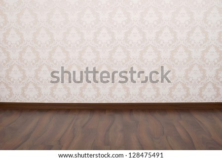 Wooden parquet floor and wallpaper on a wall - stock photo