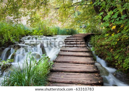 Wooden path along the stream in forest - stock photo