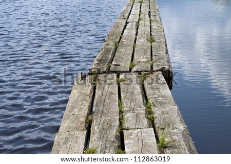 Wooden path floating on calm water. Large DOF. - stock photo