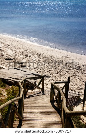 Wooden path leading down to the beach. Clear blue ocean in the background - stock photo