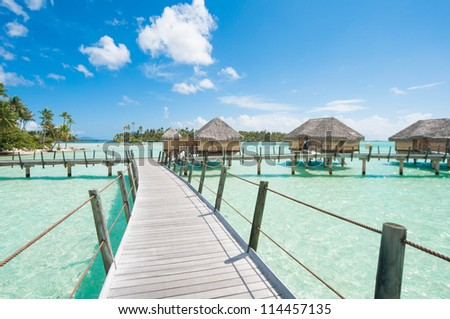 Wooden path to  bungalows in Tahiti - stock photo