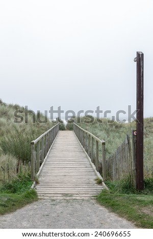 Wooden pathway crossing the dunes towards the beach and the vanishing point in the horizon. The low contrast reflects a dreamy desire for a relaxed destination. The gray sky allows for a copy space. - stock photo