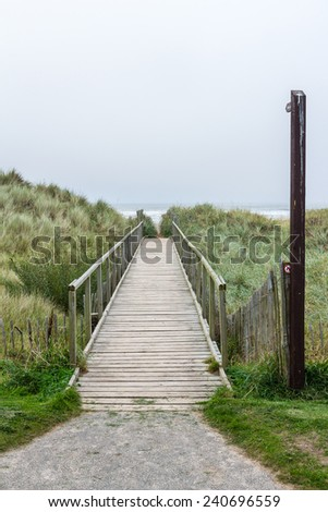 Wooden pathway crossing the dunes towards the beach. The footpath rises towards the vanishing point in the horizon. The loneliness promises a escape to relaxation. The gray sky allows for a copy space - stock photo