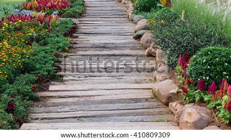 wooden pathway in park with garden - stock photo