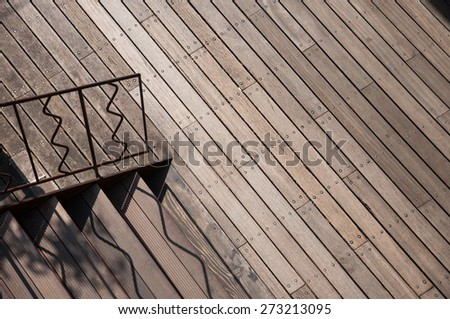 Wooden pathway nearby stair connected to up stair