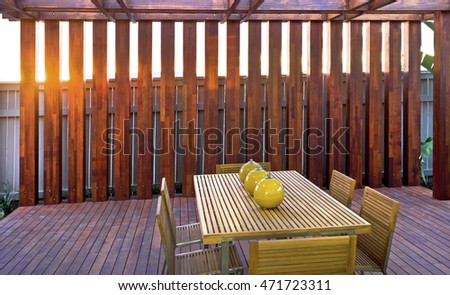 Wooden patio with chairs and ball lamps on the table at sundown light spreading through the pillars and floor