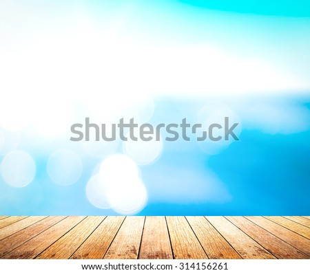 Wooden paving with blurred bokeh sea water and blue sky texture background. - stock photo