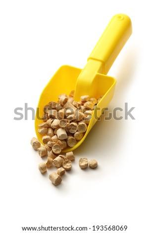 Wooden pellets on yellow plastic shovel - stock photo