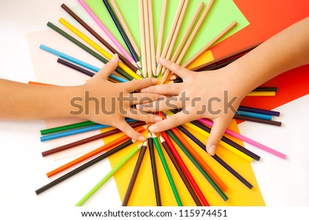 Wooden pencils and two children's hands from above. Paper in more colors in the background. Top view. - stock photo