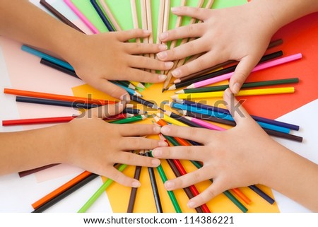 Wooden pencils and two pairs of children's hands from above. Paper in more colors in the background. Top view. - stock photo
