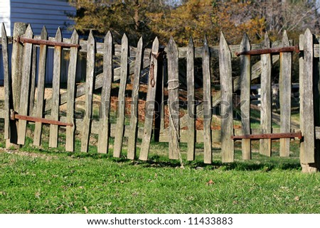 wooden picket fence with grass and trees.