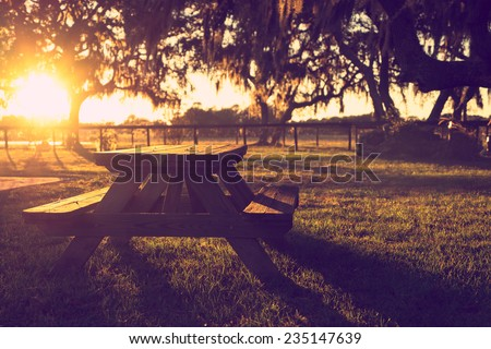 Wooden picnic table in field with trees at sunset sunrise golden hour looking peaceful serene meditative warm relaxing restful with a retro vintage cross processed filter - stock photo