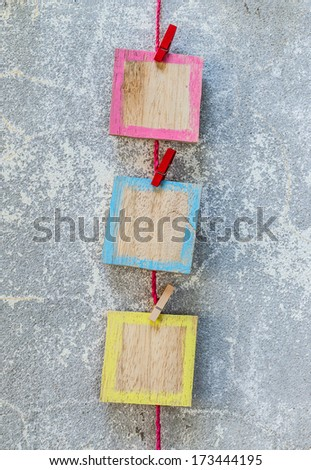 wooden picture frame hanging on clothesline on cement background. - stock photo