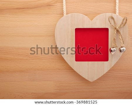 Wooden picture frame with love heart on wooden background. - stock photo