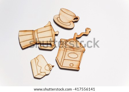 Wooden pieces cut out in the forms of coffee grinder, cup and a pie on white background. Morning coffee concept. - stock photo