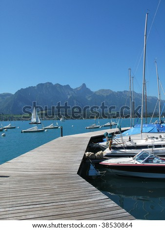 Wooden pier against lake Thun and Alps. Switzerland - stock photo