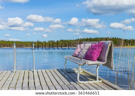 Wooden pier and cozy romantic bench with soft blanket and pillows on a background of the  beautiful lake and forest at sunny day.Scenic natural landscape.The land of lakes.Finland.Europe.