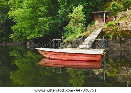 Wooden pier and red boat on the river - reflection in the river - stock photo