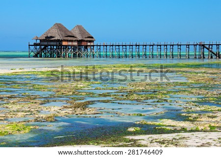 Wooden pier and thatched roofs on a tropical beach, Zanzibar island - stock photo