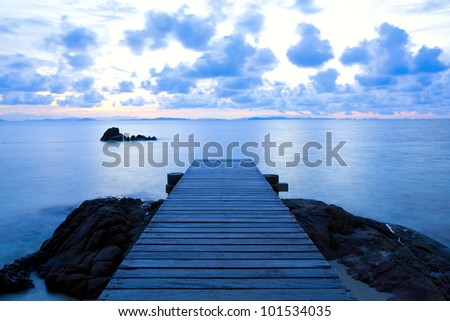 Wooden pier at the beach in perspective - stock photo