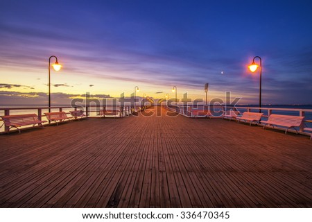 wooden pier by the sea lit by stylish lamps at night  - stock photo