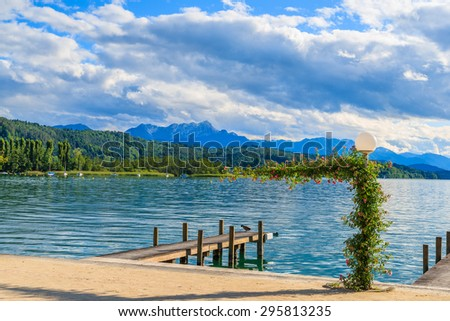 Wooden pier for mooring boats on Worthersee lake on beautiful summer day, Austria - stock photo