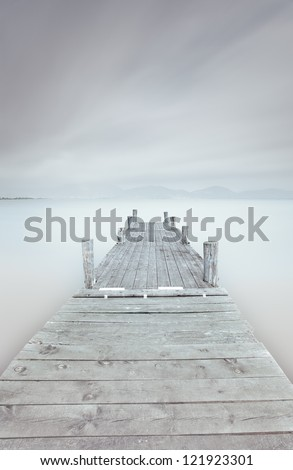 Wooden pier in a cloudy and foggy mood. A long exposure photography taken in autumn. - stock photo