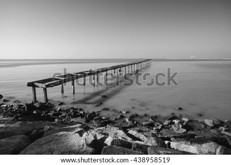 wooden pier in caribbean sea with beautiful blue sky and copy space area. - stock photo