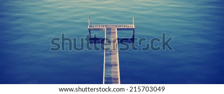 Wooden pier / jetty stretches out into an idyllic ocean with Instagram style filter - stock photo