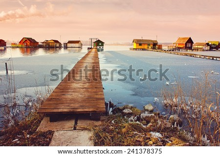 Wooden pier leading to fishing cottages on Bokod lake - stock photo