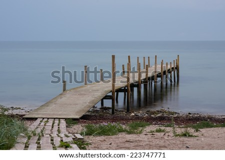 Wooden pier on beach in a gloomy predawn - stock photo
