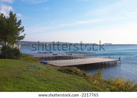 Wooden pier on coast of Black Sea - stock photo