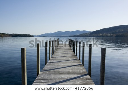 Wooden pier on Lake George with mountains in the background.