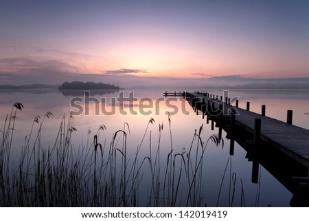 wooden pier on lake in summer morning - stock photo